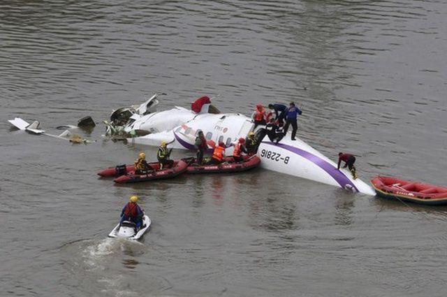 Rescuers carry out a rescue operation after a TransAsia Airways plane crash landed in a river, in New Taipei City, February 4, 2015. At least 11 people were killed and up to 19 were missing after a Taiwanese TransAsia Airways plane with 58 passengers and crew on board crashed into a river shortly after taking off from a downtown Taipei airport on Wednesday, officials said. REUTERS/Stringer (TAIWAN - Tags: TRANSPORT DISASTER TPX IMAGES OF THE DAY) TAIWAN OUT. NO COMMERCIAL OR EDITORIAL SALES IN TAIWAN. CHINA OUT. NO COMMERCIAL OR EDITORIAL SALES IN CHINA