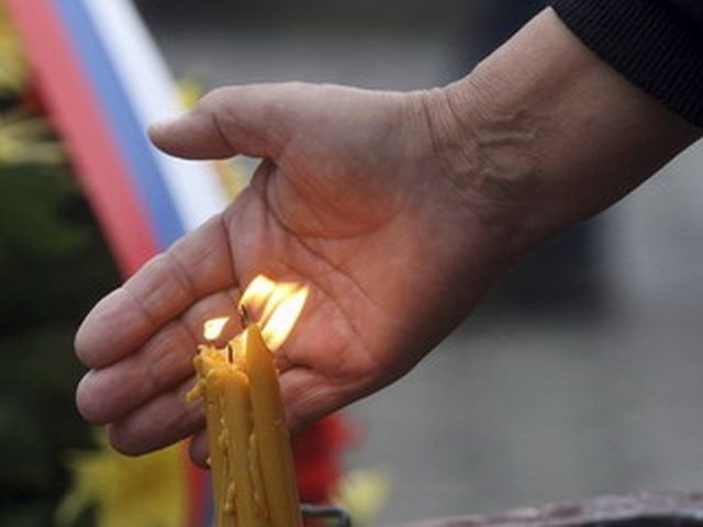 A person places his hand near candles during a ceremony to commemorate the Day of Missing Persons of Republic of Srpska at the Soldiers Monument in Banja Luka September 15, 2008.  REUTERS/Ranko Cukovic (BOSNIA & HERZEGOVINIA)