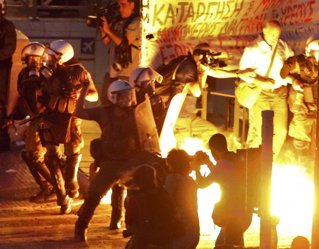 Riot police stand amongst the flames from exploded petrol bombs thrown by a small group of anti-establishment demonstrators in front of parliament in Athens, Greece July 15, 2015. Prime Minister Alexis Tsipras battled to win lawmakers' approval on Wednesday for a bailout deal to keep Greece in the euro, while the country's creditors, pressed by the IMF to provide massive debt relief, struggled to agree a financial lifeline. REUTERS/Jean-Paul Pelissier