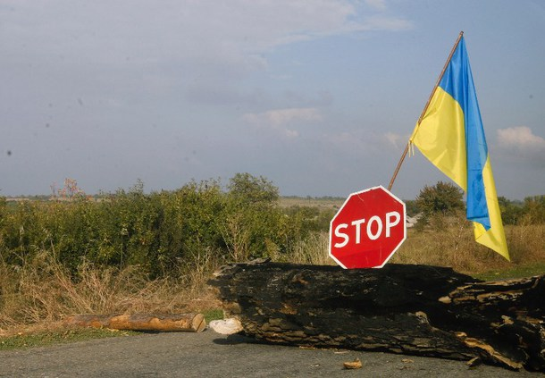 The Ukrainian flag and a Stop sign are seen on a road near Ukrainian check point in the Donetsk region on September 26, 2014. The European Union on Friday unveiled an interim deal meant to end Russia's latest gas war with Ukraine which could see a return of supplies to the crisis-hit nation and a renewal of trust between the rival neighbours.  AFP PHOTO/ANATOLII BOIKO