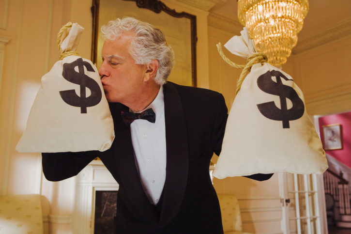 Wealthy man kissing money bags